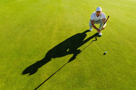 Golf player aiming shot with club on course