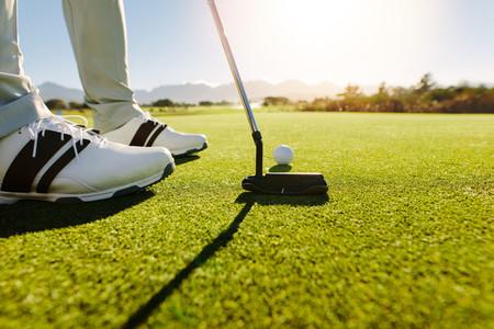 Golfer putting golf ball to hole