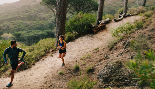 Couple of fit athletes running on mountain path
