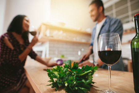 Glass of red wine on kitchen counter with couple in background