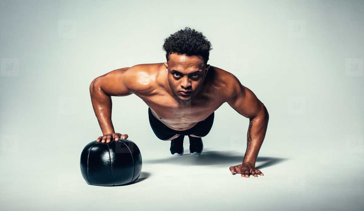 Young fit man doing push up on medicine ball