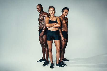 Group of muscular people standing on grey background