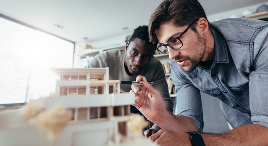Two male architects discussing over house model