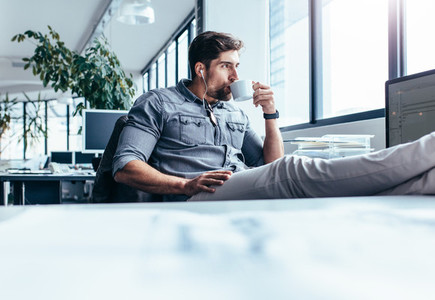 Young man drinking coffee during break in office