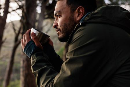 Male hiker taking rest and having coffee outdoors