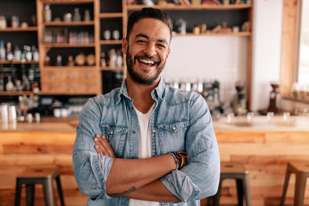 Happy young man standing with his arms crossed in a cafe