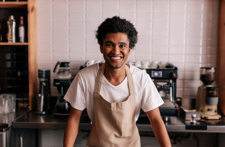 Happy young barista standing at cafe counter