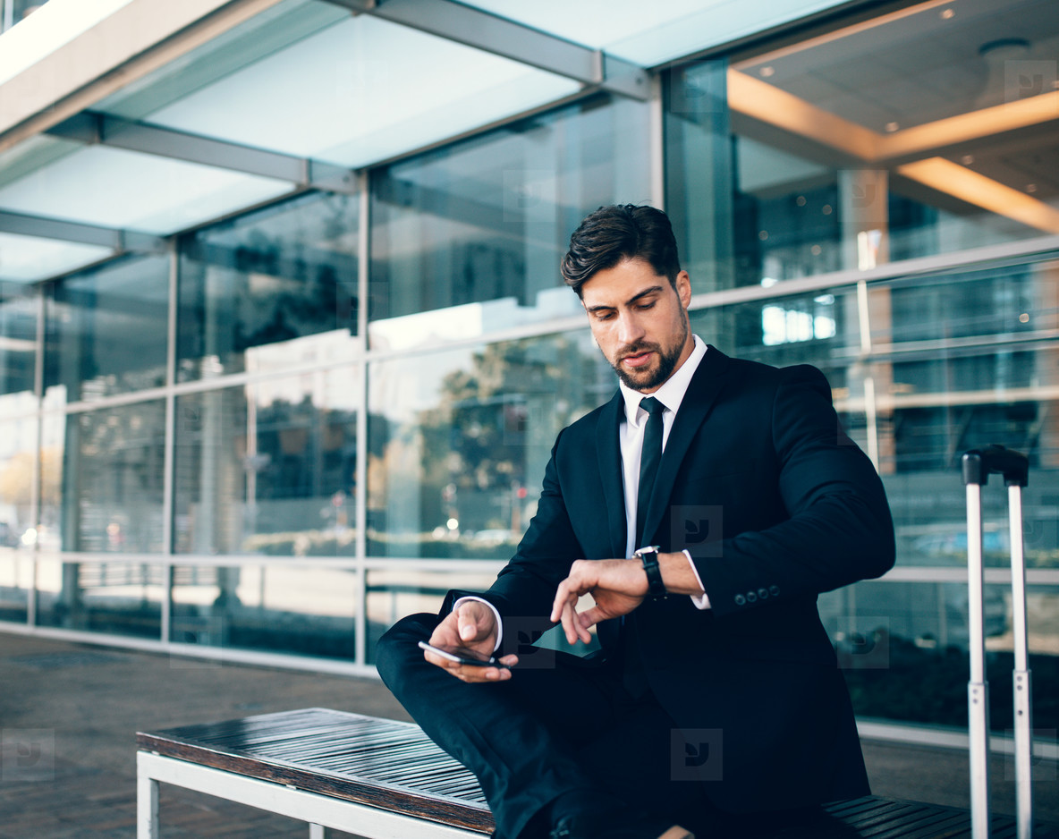 Young businessman checking time at airport