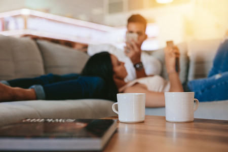 Coffee cups on table with couple relaxing in background