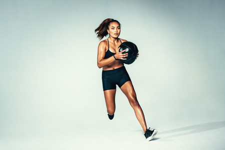Fit woman running with medicine ball