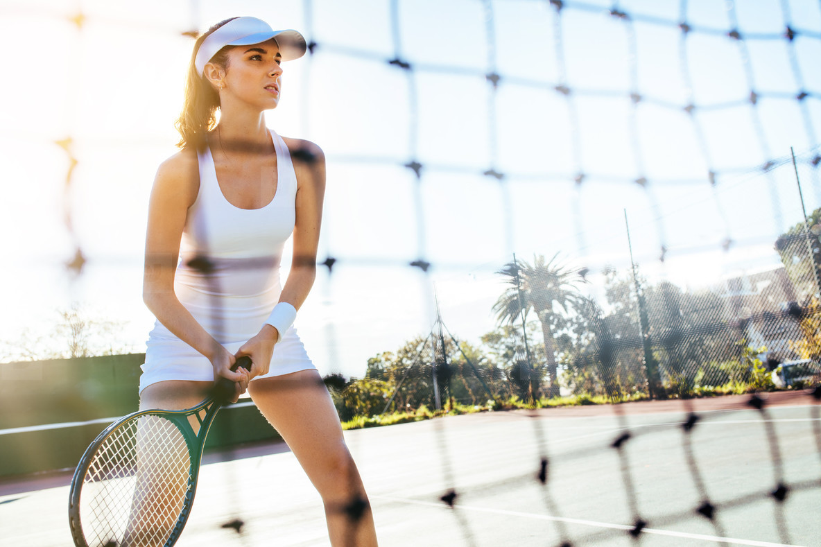 Beautiful tennis player with racket on court