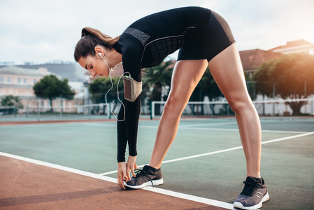 Sportswoman doing warmup exercise on tennis court