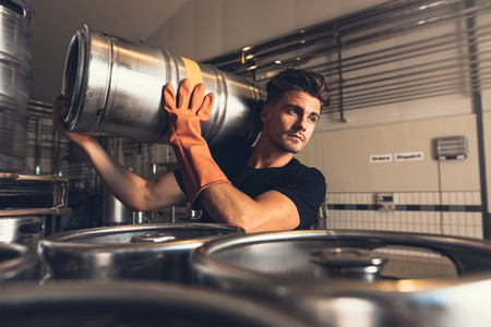 Brewer carrying keg at brewery factory