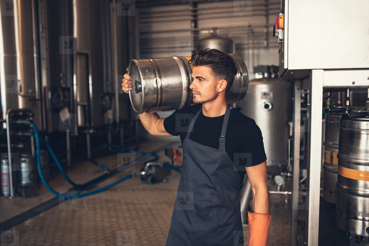 Young male brewer carrying keg at brewery