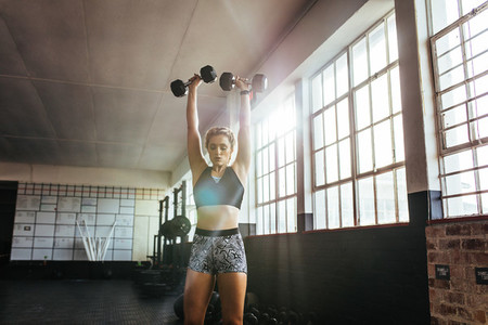 Young woman working out at the gymnasium using dumbbells