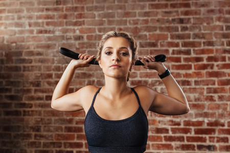 Young woman doing neck exercises using a band