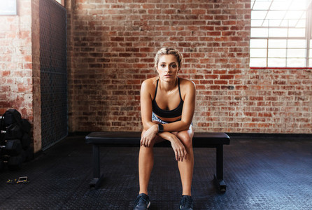 Woman in sportswear sitting on bench at the gym