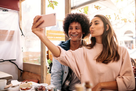 Young couple taking selfie with smart phone at cafe