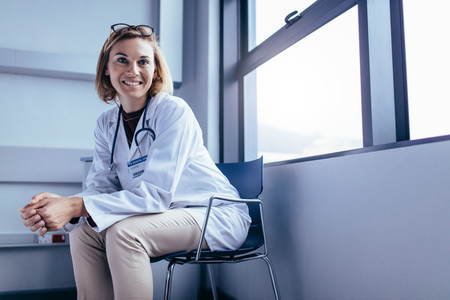 Smiling female doctor sitting in hospital room