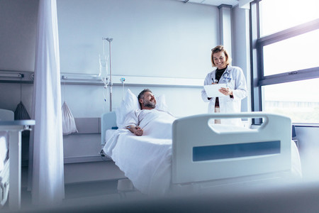 Doctor attending sick patient in hospital bed