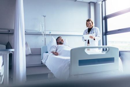 Doctor attending sick patient in hospital bed