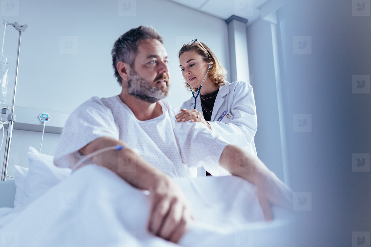 Hospitalised man getting examined by female physician