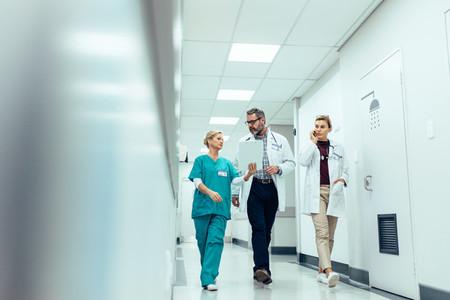 Group of medics discussing along hospital corridor