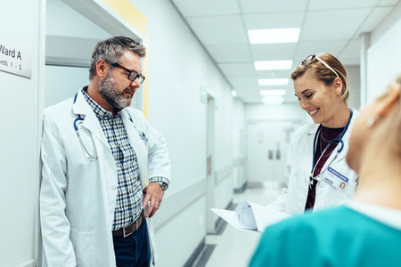 Doctor with colleagues standing in hospital hallway