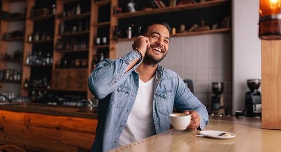 Happy young guy at cafe speaking on phone