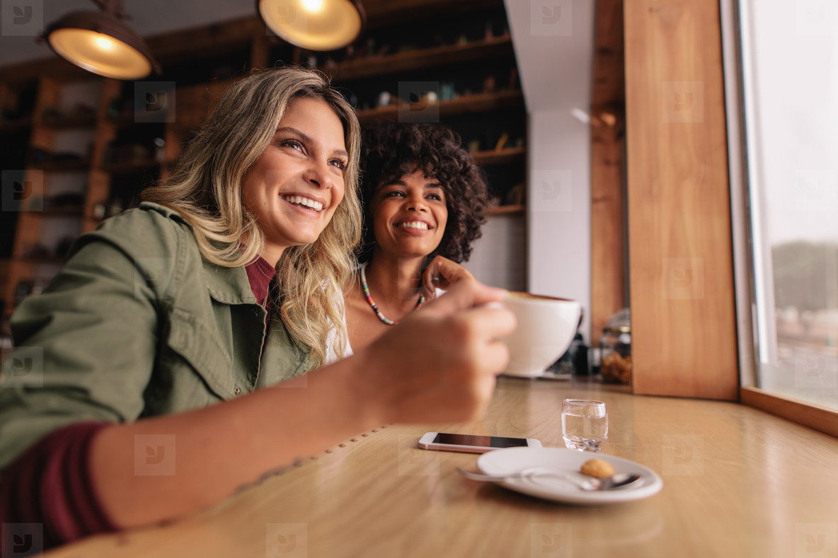 Two young woman sitting at cafe and having coffee