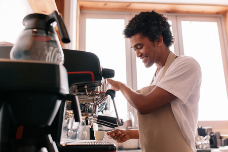 Young man making coffee with an espresso coffee machine at cafe