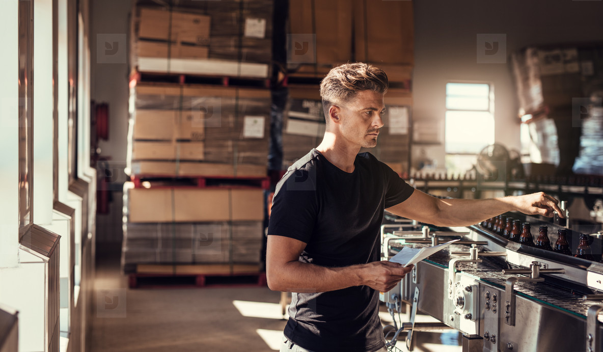 Young man working at brewery plant