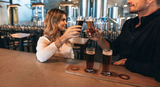 Couple at the bar with different varieties of craft beers