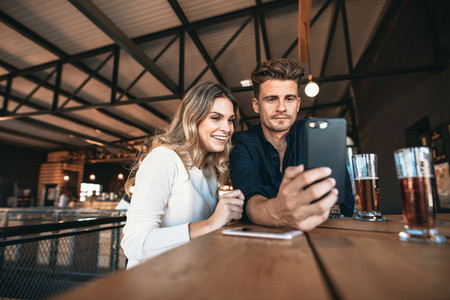 Young couple at the bar taking selfie with mobile phone