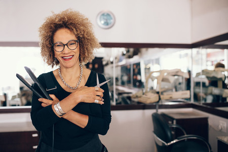 Female hairdresser at the salon holding hairdressing tools
