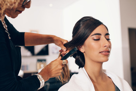 Female hair stylist working on a woman 039 s hair at salon