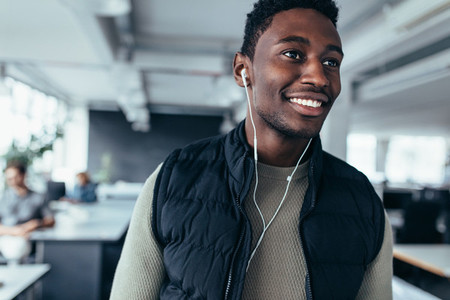 Happy african man listening music in office