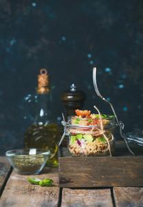 Homemade jar quinoa salad with vegetables and fresh basil