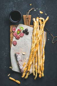 Grissini bread sticks  sausage  olives and red wine  copy space