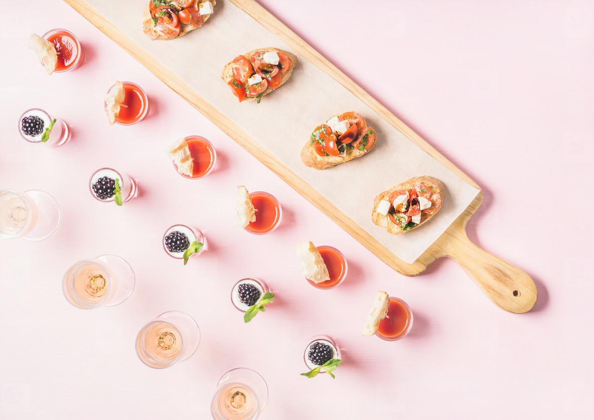 Snacks  brushetta sandwiches  gazpacho shots  desserts over pastel pink background