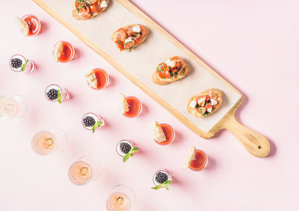 Snacks brushetta sandwiches gazpacho shots desserts over pastel pink background