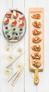 Brushettas  gazpacho shots  desserts  champagne and straws over white background