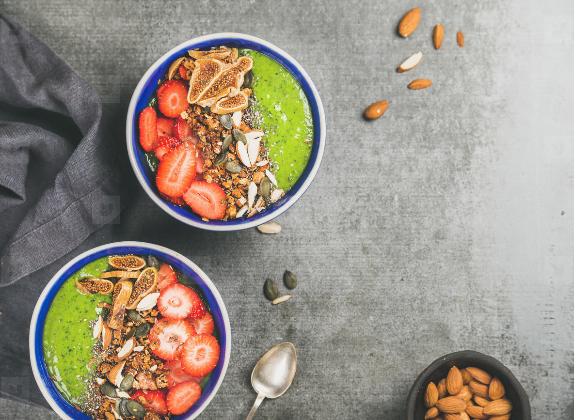 Healthy green smoothie breakfast bowls with granola  strawberry  seeds