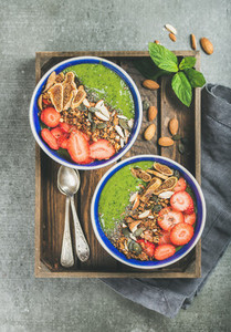 Healthy green smoothie breakfast bowls with granola  fruit  seeds