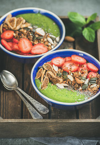 Healthy breakfast  green smoothie bowls with granola  fruit  seeds