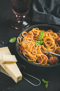 Spaghetti with meatballas  basil  parmesan cheese in black plate