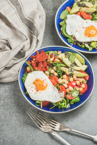 Healthy breakfast with fried egg  chickpea  vegetables  seeds and greens
