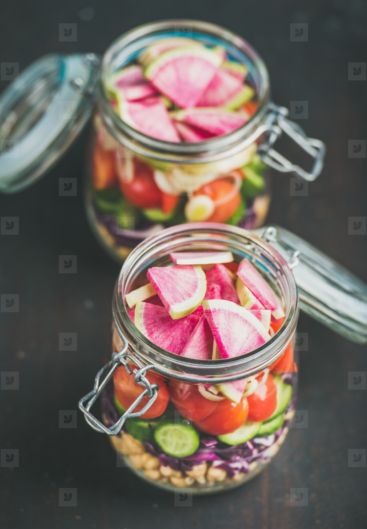 Vegetable  chickpea sprout salad in jars  dark scorched wooden background