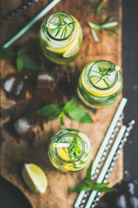 Healthy infused citrus sassi water in glass bottles with rosemary