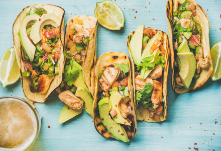 Healthy corn tortillas and beer over blue wooden background
